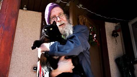 """Pertti """"Veltto"""" Virtanen kissansa kanssa kotonaan Lempäälässä."""