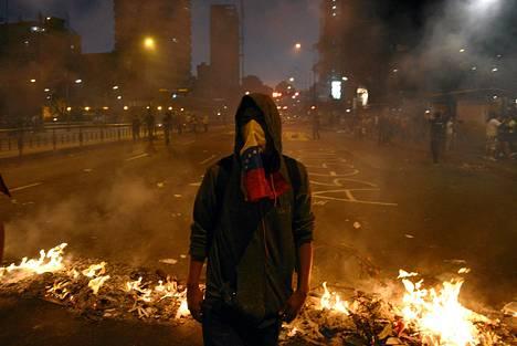 Mielenosoittaja seisoi barrikaadien edessä Caracasissa lauantain vastaisena yönä.