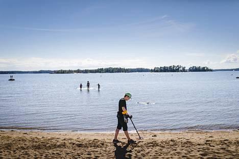 Kallahdenniemen uimarannalla voi kahlata kauas, sillä ranta on matala. Oskari Kotamäki etsii hiekasta koruja ja kolikoita metallinpaljastimellaan.