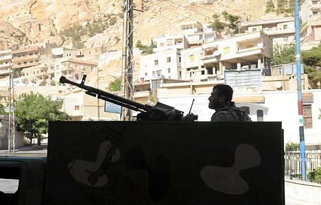 Syyrialaissotilas odotti konekiväärin takana lauantaina Maalulan kaupungissa.