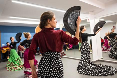 Oppilaat harjoittelevat viuhkan ja laahushameen liikkeitä Cristina Heerenin säätiön maineikkaassa flamencotaiteen koulussa Sevillassa.