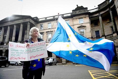 Mielenosoittaja vastustaa pääministeri Boris Johnsonin päätöstä sulkea Britannian parlamentti Skotlannin korkeimman oikeuden edessä Edinburghissa elokuussa.