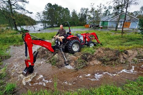 Pohjois-Carolinan Boiling Spring Lakesissa asuva mies yritti ohjata tulvavesiä pois pihapiiristään kaivinkoneen avulla lauantaina.