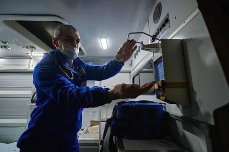 Ambulanssilääkäri Omar Umarilahanov desinfioi kätensä ennen aamun ensimmäistä hälytystä. Hän työskentelee yksityiselle Coris-ambulanssiyhtiölle, jonka kyydeistä nykyisin 80 prosenttia liittyy koronavirukseen.