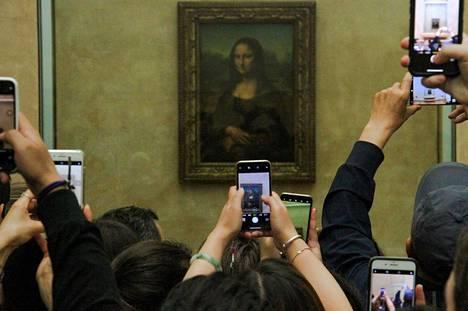 Mona Lisa vakituisella paikallaan Louvren Salle des États -salissa, jossa sitä pääsi katselamaan lähempää kuin kolmen metrin päästä.