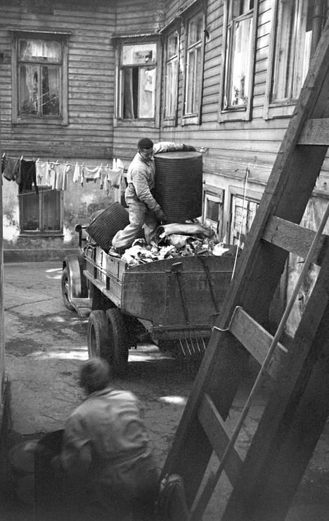 Kotitalouksien jätteet koottiin jäteastioihin, joista ne myöhemmin kuljetettiin kaatopaikalle tai poltettavaksi. Kuvassa tyhjennetään roskatynnyriä Punavuoressa 1950-luvun alussa.