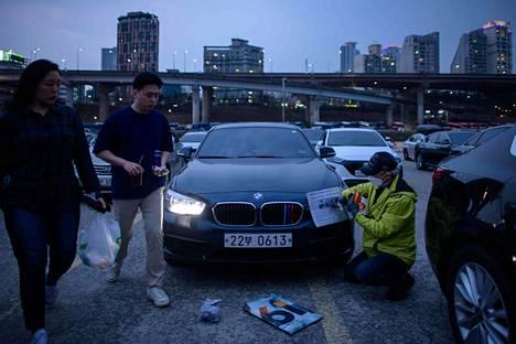 Drive-in-teatterin työntekijä kiinnittää sanomalehtiä auton valojen päälle ennen näytöksen alkamista Soulissa.