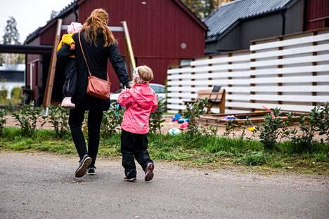 Äiti ja lapset matkalla päiväkotiin.