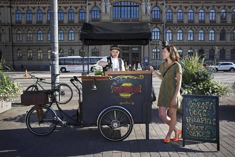 Juha Teerimäki kokkaa mäskistä kehiteltyä katuruokaa. Annika Nummela hoitaa ruokakärryn kassaa.