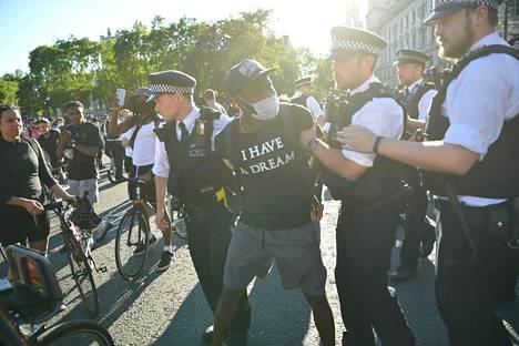 Poliisit pidättämässä miestä Lontoon mielenosoituksissa 31. toukokuuta.