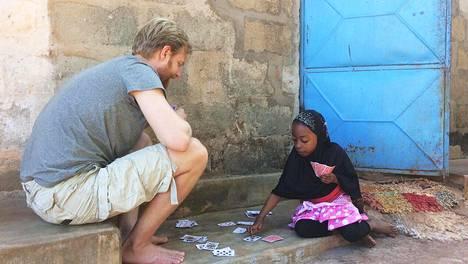 Tanskalainen Brian pelasi korttia pikkutytön kanssa Sansibarin Kizimkazin kalastajakylässä.