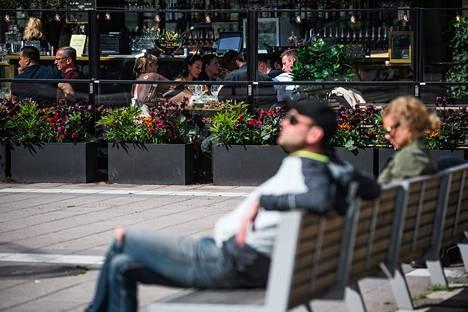 Ihmiset istuskelivat ravintolassa ja puistossa likellä toisiaan Tukholmassa 8. toukokuuta.