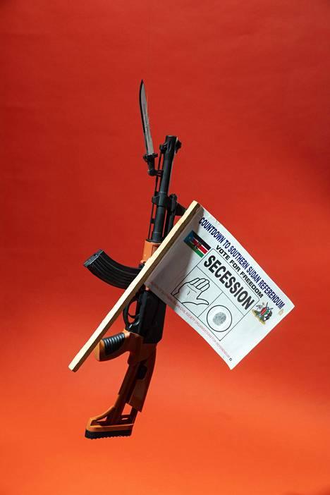 Muovinen AK-47-kivääri ja itsenäistymisen puolesta liputtava viiri ovat muistoja Etelä-Sudanista vuodelta 2011.