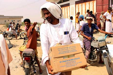 Jemeniläiset kantoivat Maailman ruokaohjelman WFP:n ruoka-avustuspaketteja lähellä Saudi-Arabian rajaa.