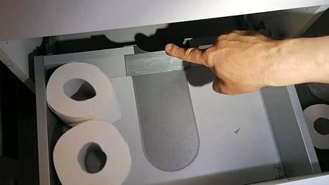 Pienyrittäjä Jouko Lehtomäki painaa 3d-tulostimellaan tehdyn levyn allaskaappiin. Hopeanvärisen levyn vapauttama tila on normaalitilanteessa putkien valtaama.