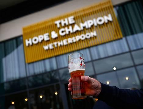 Mies piteli oluttuoppia The Hope and Champion -pubin ulkopuolella M40-moottoritien varrella tiistaina.