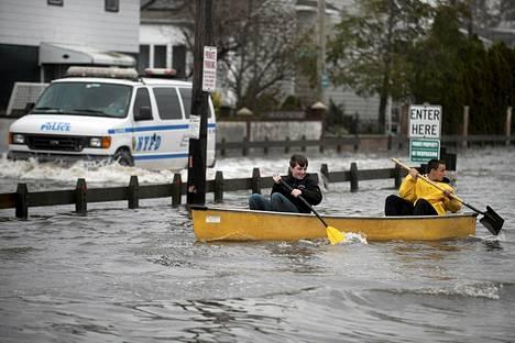 Asukkaat meloivat kanootilla tulvaveden valtaamassa Queensissä New Yorkissa tiistaina.