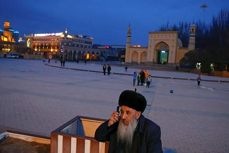 Mies puhuu puhelimeen moskeijan edustalla Kashgarin vanhassa kaupungissa Xinjiangin uiguurialueella.