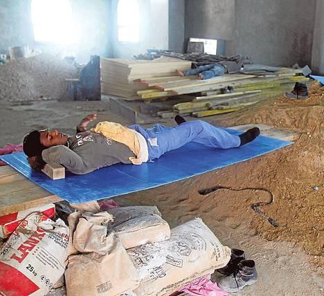 Rakennustyöntekijät lepäsivät lounastauolla Qatarin Dohassa kesäkuussa 2012. Siirtotyöläisten olot ovat kurjat.
