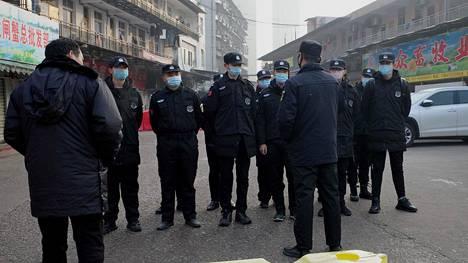 Vartijat seisoivat suljetun Huananin kauppatorin edessä 11. tammikuuta.