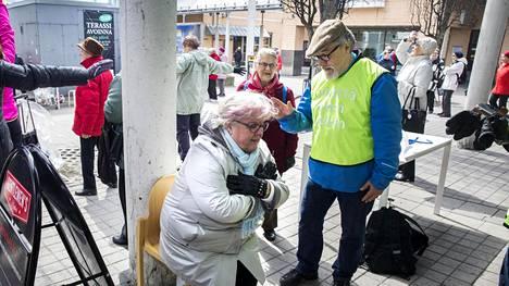 Pekka Isaksson ohjasi Anne Ruikkaa Unelmien liikuntapäivän kunto- ja tasapainotestissä Kontulassa.