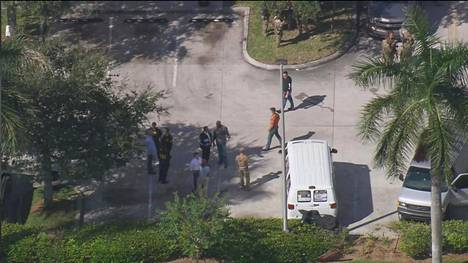 Poliisit tutkivat perjantaina Miamin lähellä pakettipommien lähettäjäksi epäillylle kuuluvaa vaaleaa pakettiautoa.