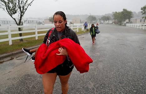 Vapaaehtoinen pelastustyöntekijä Maggie Belgie kantoi sylissään tulva-alueelta evakuoitavaa lasta Pohjois-Carolinan Lumbertonissa lauantaina.