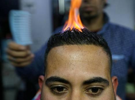 Palestiinalainen parturi Ramadan Odwan esittelee tekniikkaansa, jossa hiuksia suoristetaan ja kampausta muotoillaan tulen avulla. Esittely järjestettiin Gazan Rafahissa viime viikolla.