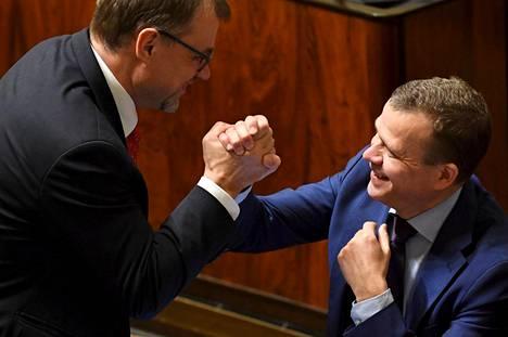 Pääministeri Juha Sipilä (kesk) ja valtiovarainministeri Petteri Orpo (kok) löivät kättä eduskunnan täysistunnossa perjantaina sen jälkeen, kun Tilastokeskus oli kertonut työllisyysasteen trendin nousseen 72 prosenttiin.