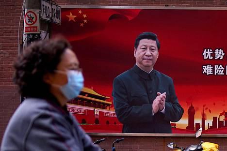 Hengitysmaskilla varustautunut nainen kulki presidentti Xi Jinpingin kuvan ohi Shanghaissa maaliskuussa.