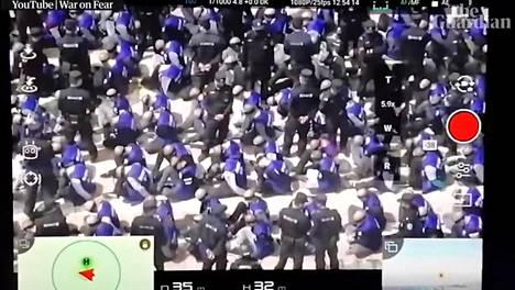 Kuvakaappaus The Guardian -lehden videolta. Lennokilla kuvatulla videolla näkyy satoja ihmisiä silmät sidottuina ja kahlittuna Xinjiangissa.