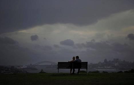 Pariskunta seuraa myrskyn nousemista Sydneyn satama-alueella maanantaina.