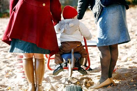 Naispari lapsen kanssa puistossa.