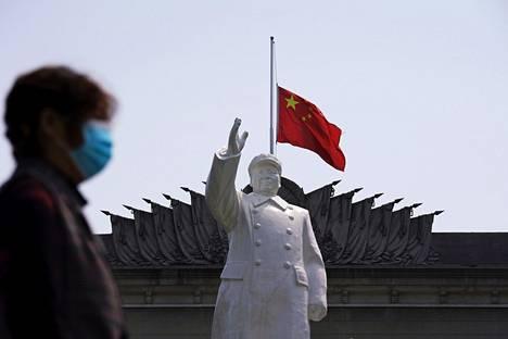 Kiinan lippu puolitangossa Kiinan entistä johtajaa Mao Tsetungia kuvaavan patsaan takana Wuhanissa 4. huhtikuuta. Kiinassa pidettiin kansallinen surupäivä koronaan kuolleille vuosittaisen hautojenlakaisupäivän yhteydessä.
