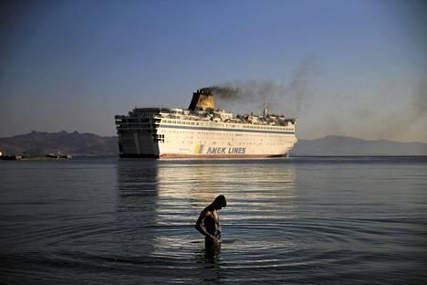 Siirtolainen peseytyi meressä keskiviikkona Kosin saarella Kreikassa. Taustalla näkyvä laiva oli viranomaisten mukaan lähdössä Kosilta Thessalonikiin täynnä Syyriasta saapuneita siirtolaisia. Laiva oli sitä ennen toiminut satamassa siirtolaisten tilapäisenä majapaikkana.