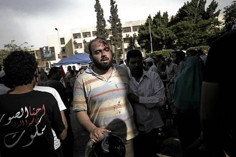 Perjantain kahakoissa päähänsä vammoja saanutta mielenosoittajaa viedään ambulanssiin Kairossa.