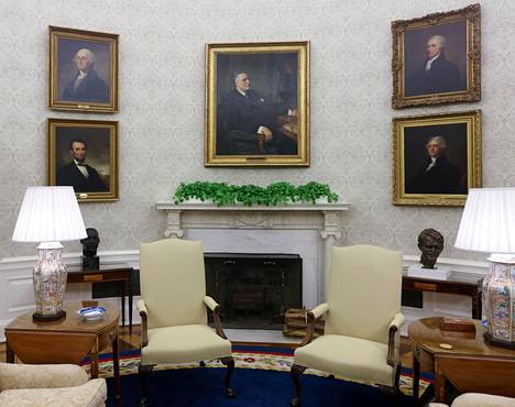 Joe Biden looks directly behind his desk toward a portrait of Franklin D. Roosevelt.  On the left are George Wasjington and Abraham Lincoln, on the right are the brawlers Thomas Jefferson and Alexander Hamilton.
