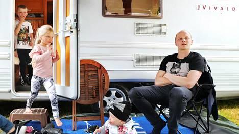 Oululainen Koposen perhe pitää karavaanarielämän kiireettömyydestä. Vasemmalla Johanna Kurtti-Koponen, vaunussa Alvar Koponen, ulos tulossa Iines Koponen ja maassa istuu Sienna Koponen. Oikealla Jyrki Koponen.