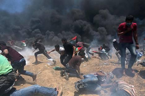 Gazalaiset mielenosoittajat hakivat suojaa Israelin tulitukselta maanantaina.