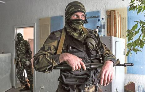 Aseistautuneet miehet seisoivat vartiossa Luhanskin turvallisuuspalvelun SBU:n päämajassa torstaina.