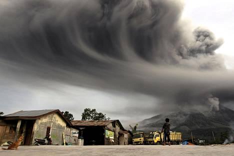 Mount Sinabung sylki tuhkaa Karossa Indonesiassa maanantaina. Ilmakehään nouseva tuhkapilvi näkyi hyvin Sibintun kylästä.