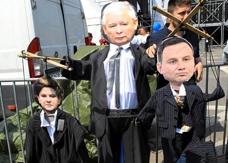 Laki ja oikeus -puolueen johtajaa Jarosław Kaczyńskia pidetään laajalti Puolan vaikutusvaltaisimpana ihmisenä ja jopa maan tosiasiallisena johtajana. Kaczyńskia kuvaava hahmo roikotti pääministeri Beata Szydłoa ja presidentti Andrzej Dudaa kuvaavia sätkynukkeja opposition mielenosoituksessa Varsovassa toukokuussa.