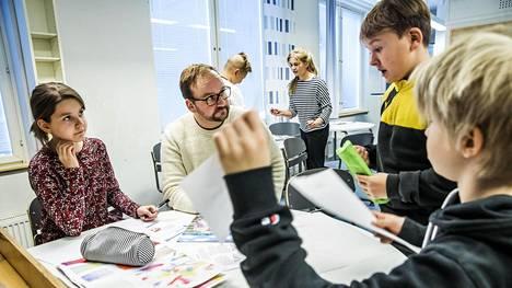 Luokanopettaja Markus Humaloja ohjaa Lotta Saaren, Jari Maunosen ja Aron Laihon työskentelyä.