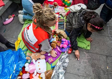 Punaisen Ristin vapaaehtoinen Irma Nilsson leikki pakolaislasten kanssa Malmön keskusaseman ulkopuolella maanantaina.