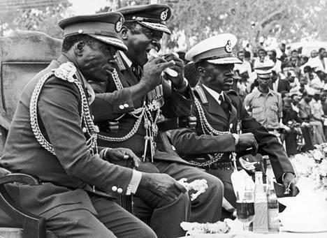 Ugandan diktaattori Idi Amin söi kanapaistia katsellessaan vallankaappauksensa vuosipäiväparaatia tammikuussa 1978 Ugandan Kobokossa. Hänen oikealla puolellaan istui Ugandan puolustusministeri Mustafa Afrisi.