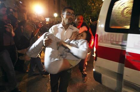 Palestiinalaismies kantaa Israelin iskuissa haavoittunutta naista ambulanssiin Gazassa.
