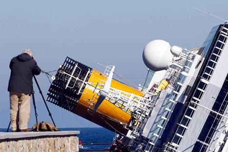 Mies otti valokuvan Goglion saaren edustalla makaavasta Costa Concordiasta helmikuussa.