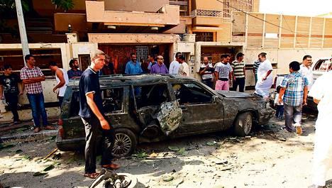 Ohikulkijat kerääntyivät katselemaan pommi-iskun tuhoja Ruotsin konsulaatin edessä Libyan Bengasissa perjantaina.