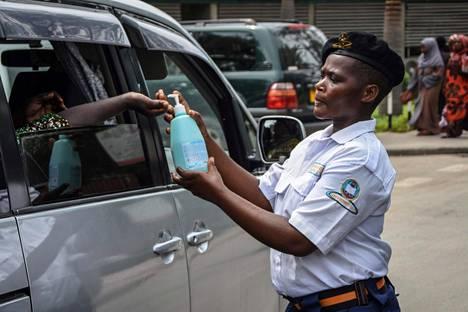 Vartija annostelee kloorivettä matkustajan käteen lähellä Muhimbilin sairaalaa Dar es Salaamin kaupungissa Tansaniassa 16. maaliskuuta.
