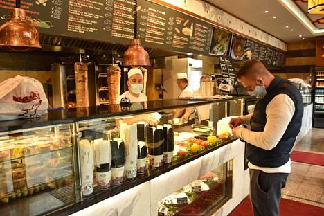 Itävallan ravintolat avautuivat tiukoin rajoituksin viime perjantaina 15. toukokuuta. Tarjoilijoilla on oltava nenän ja suun peittävät maskit.